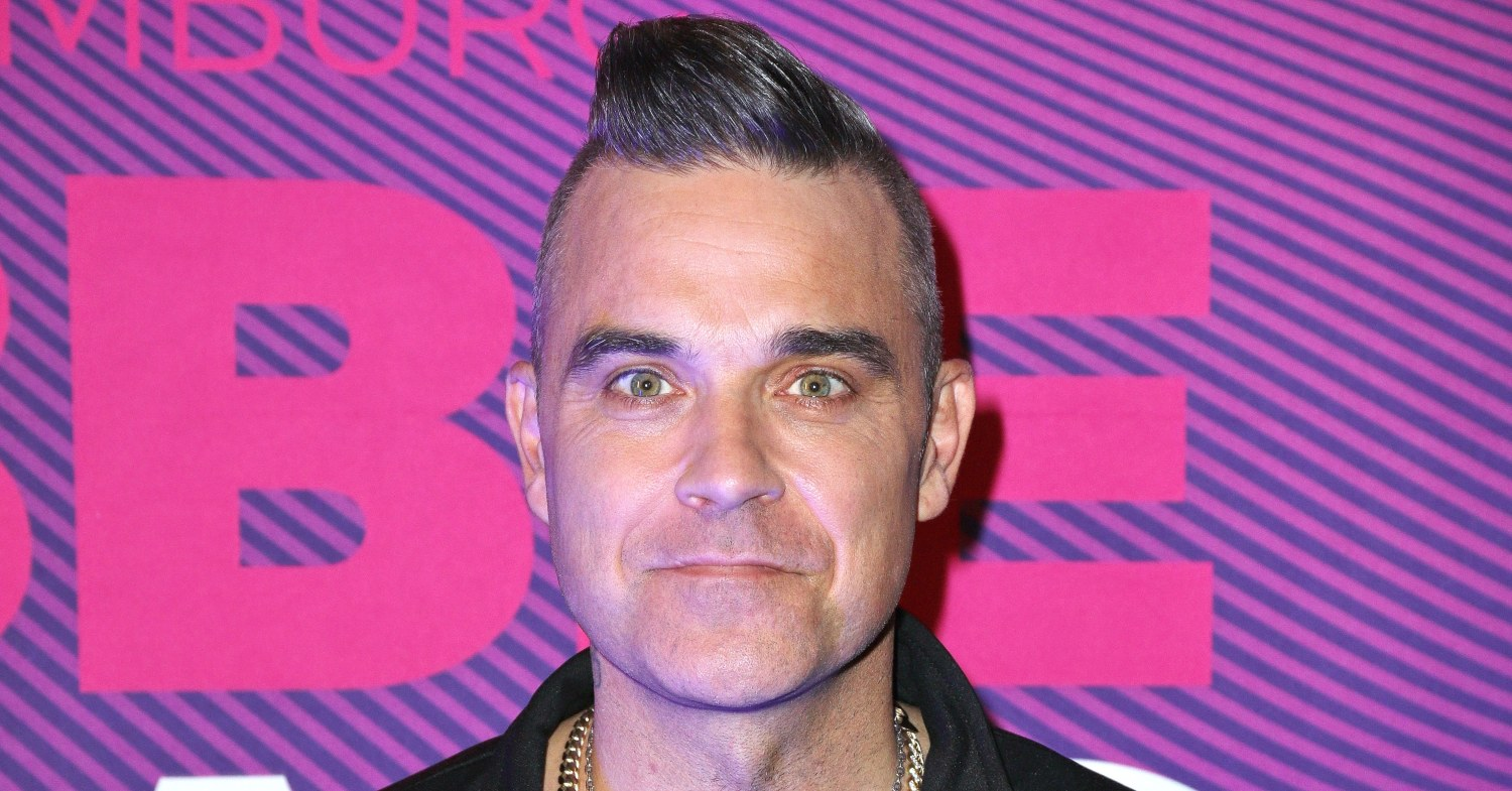 Robbie Williams stands against a purple background
