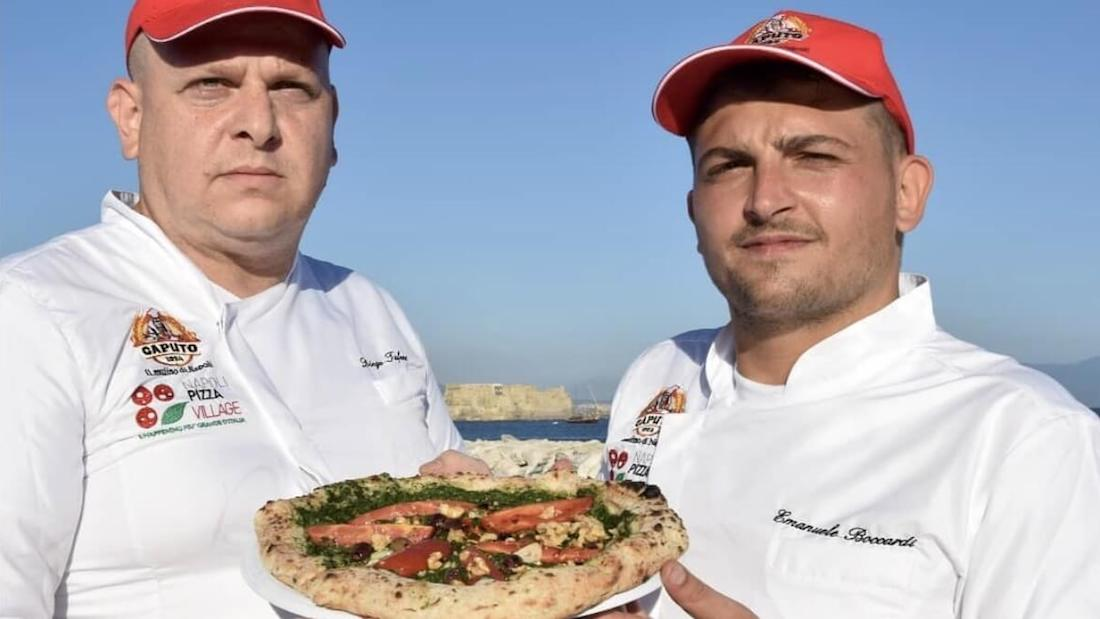 two men holding a pizza