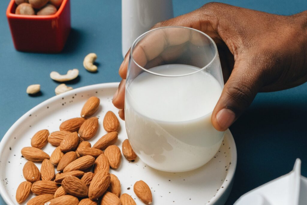 Photo of a hand holding a glass of almond milk on a plate full of almonds