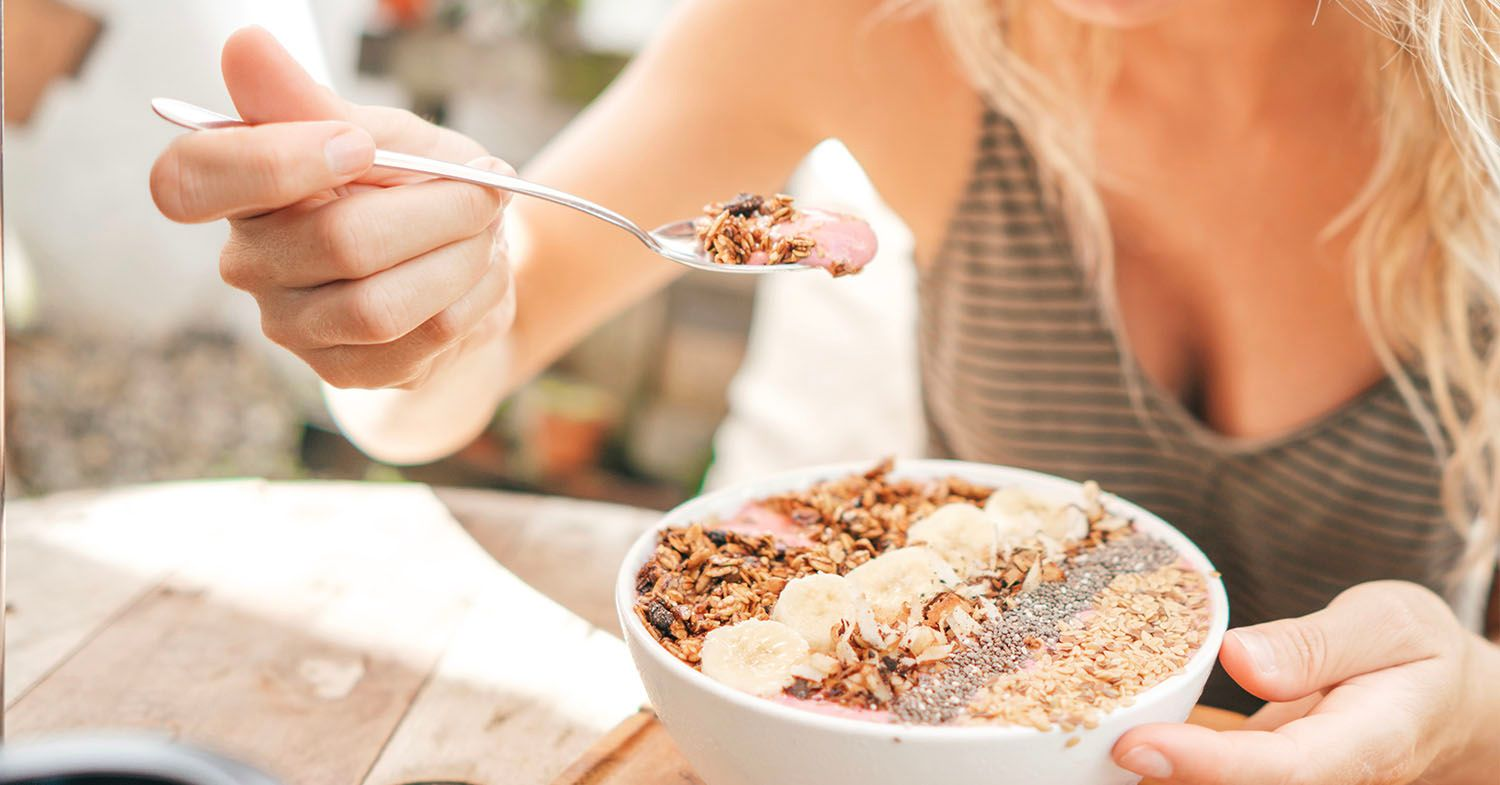 Photo shows a person with long blonde hair smiling while eating a smoothie bowl