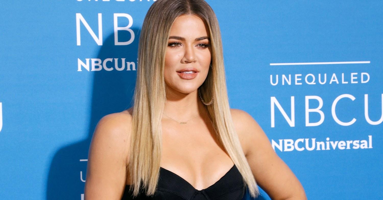 Khloe Kardashian stands against a blue background