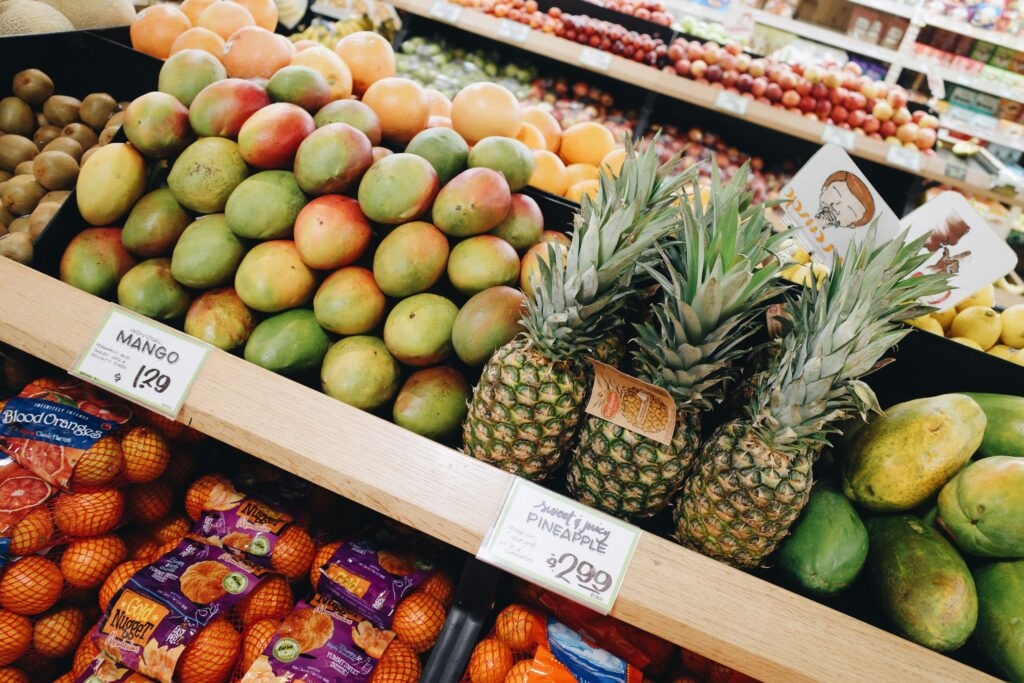A produce aisle with mangoes and pineapples.