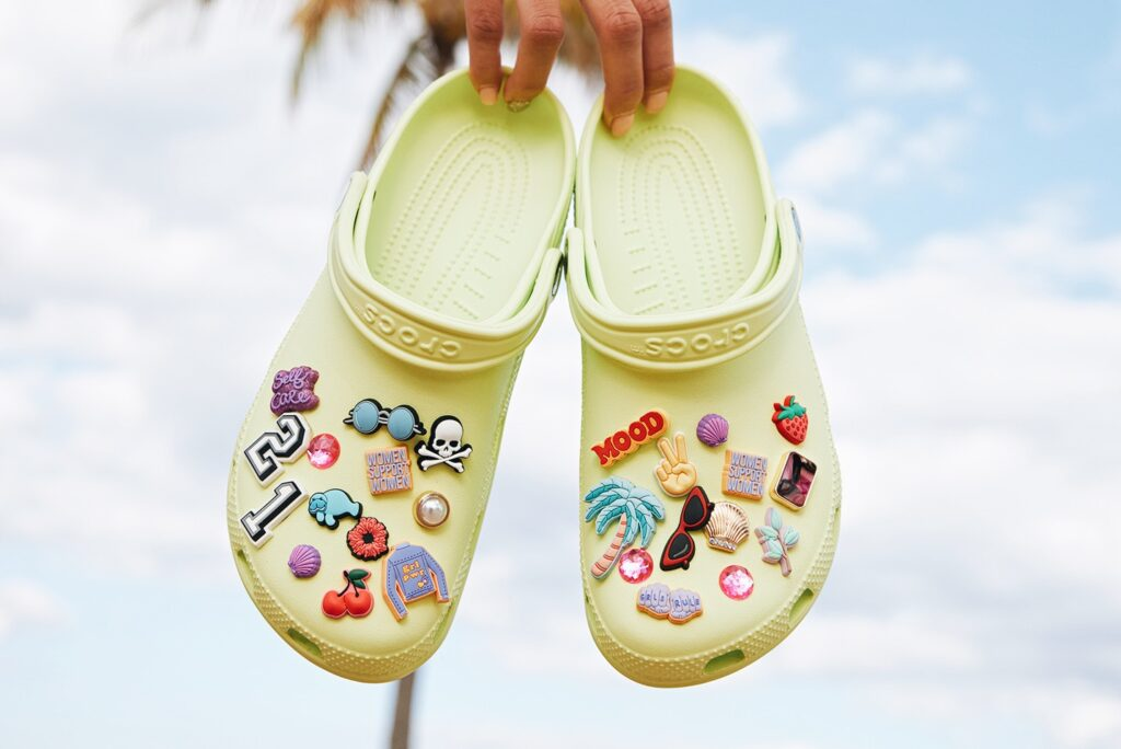 Photo of someone holding a pair of sticker-covered, pale yellow vegan crocs up by the heels against a sky and palm tree background.