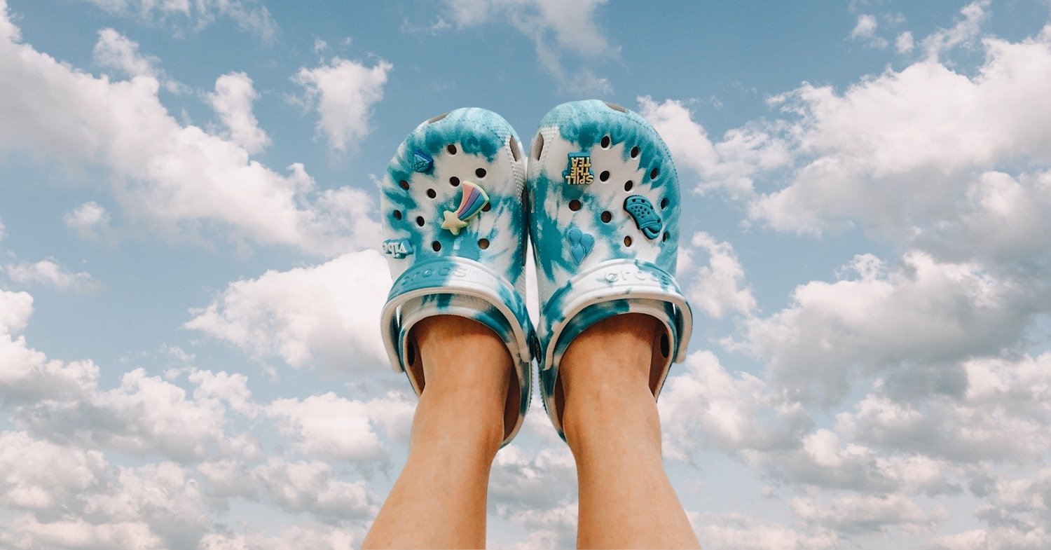 Photo of someone's feet wearing bright blue and white, tie-dyle style vegan crocs, feet held up against a sky background.