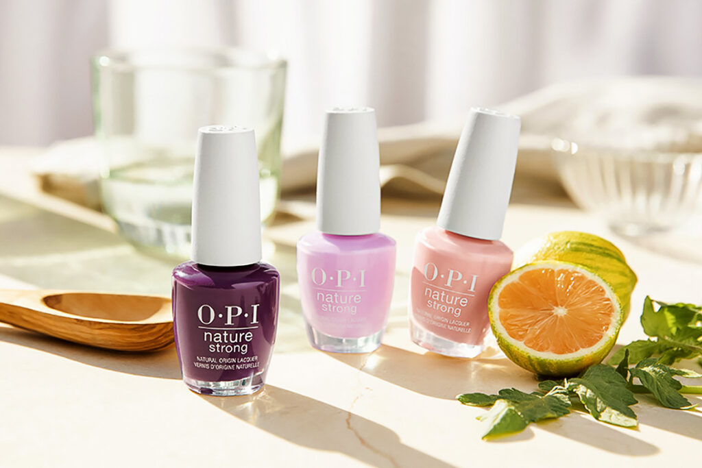 Photo shows OPI's vegan nail polish collection on a table next to citrus and leaf garnishes.