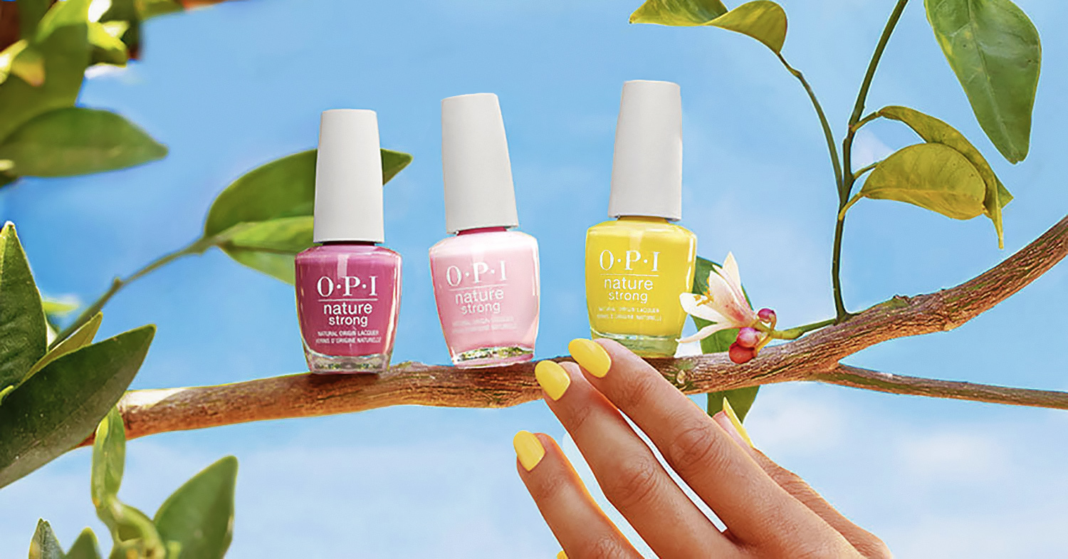 Photo shows a hand with painted nails reaching for the OPI vegan nail polish collection as it sits on a branch.