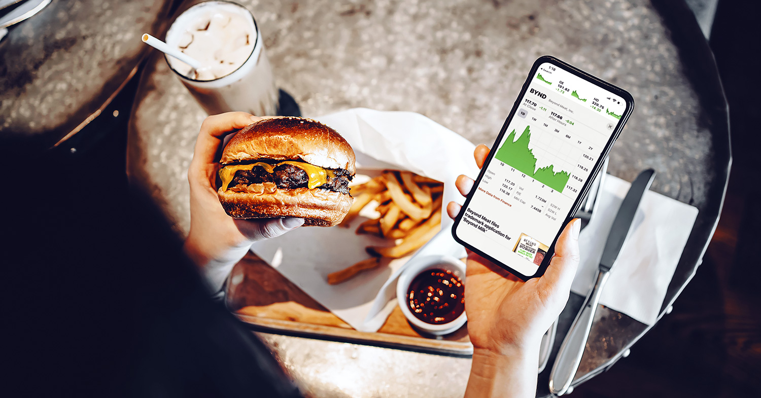 Photo shows someone eating a burger and fries with their phone in one hand, showing a graph—a plant-based market report predicts continued growth in the coming years.