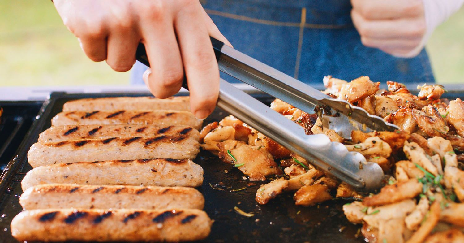 Grilling LikeMeat vegan sausages on a barbecue.
