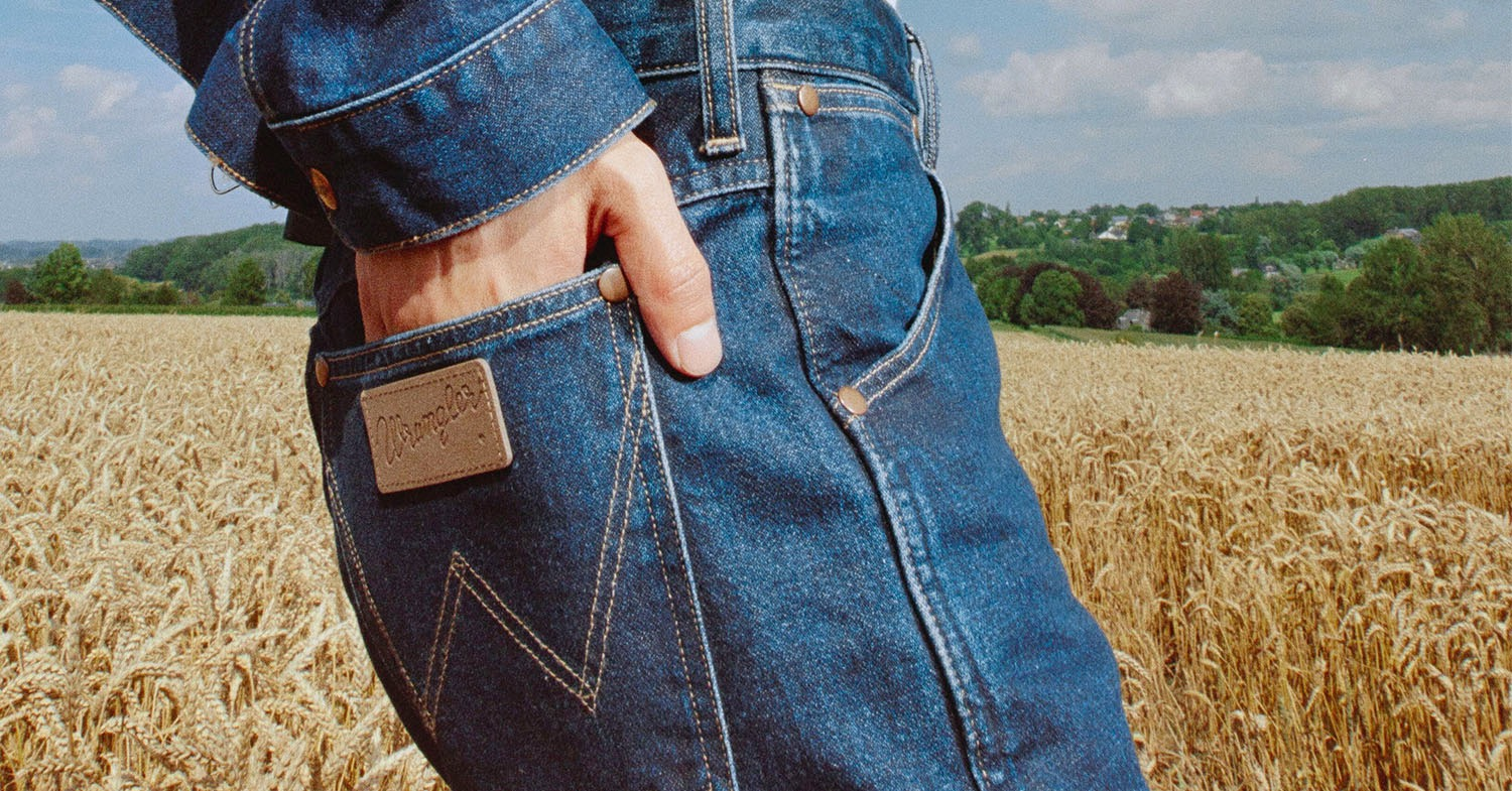 Photo shows someone wearing Wrangler jacket and jeans, focused on their mid-section and upper legs. Wrangler is introducing its most sustainable denim yet for the Fall 2021 collection.