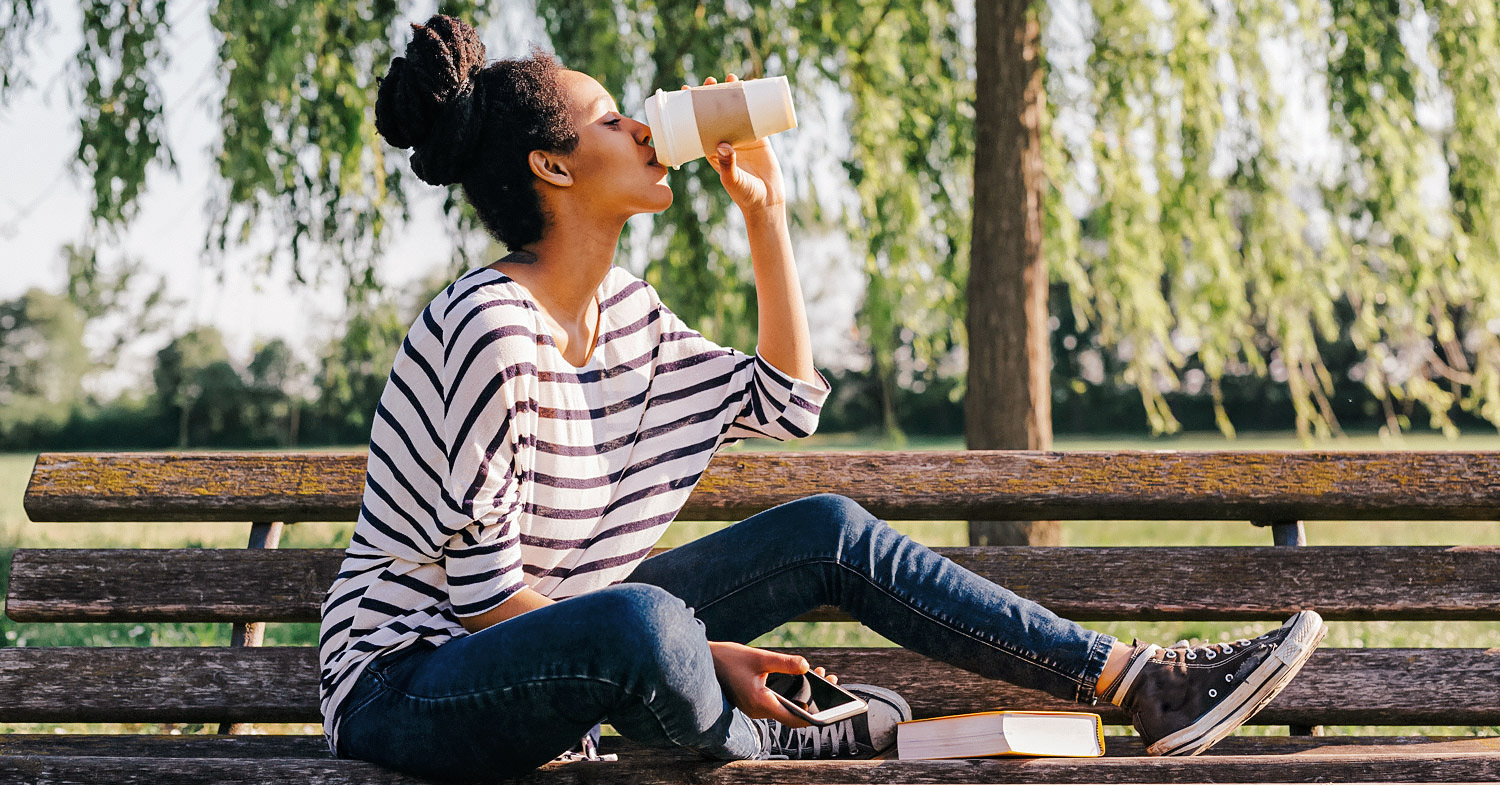 Photo shows a woman sat on a park bench drinking coffee from a takeout cup. Here are 5 caffeine-free alternatives to coffee.