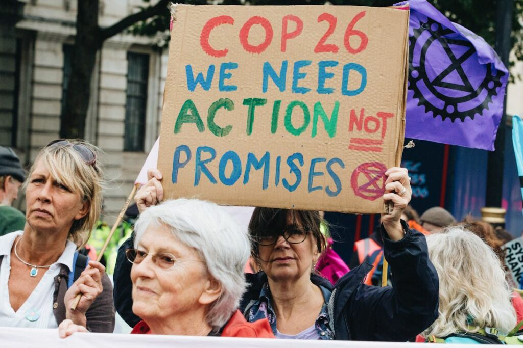Photo of protestor with the activist group Extinction Rebellion calling for COP26 to take action, not make promises