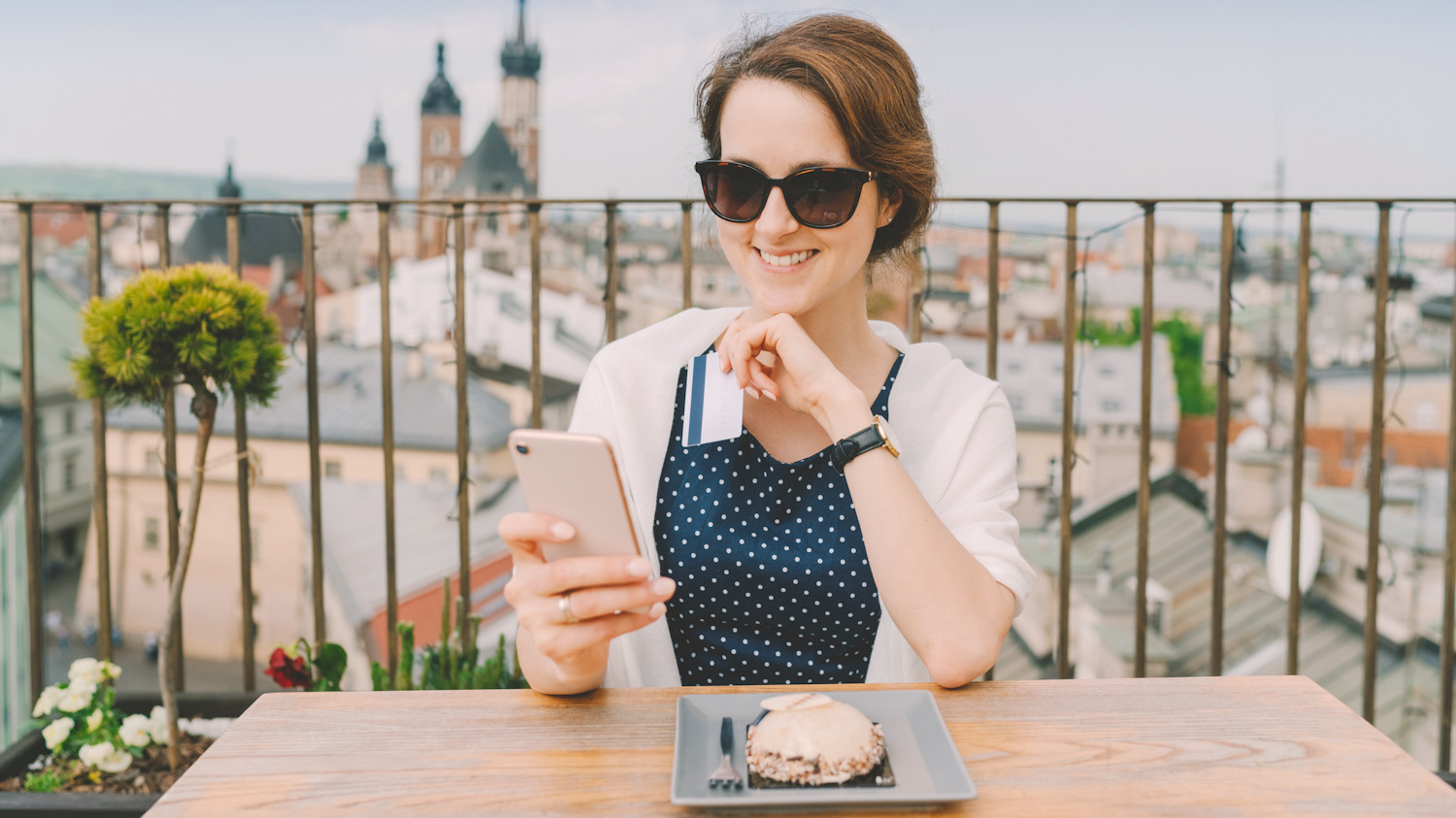 Photo shows a woman wearing sunglasses eating on a rooftop and using her phone. Google has just made it possible to search for hotels by sustainability rating.
