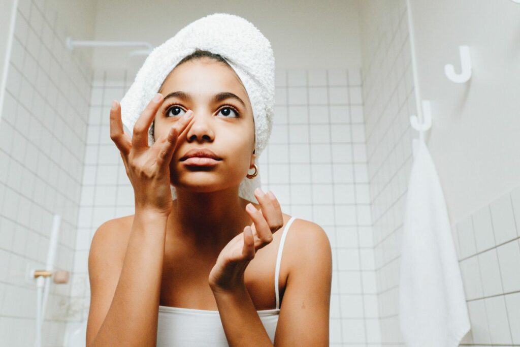 A woman applying skincare in the bathroom