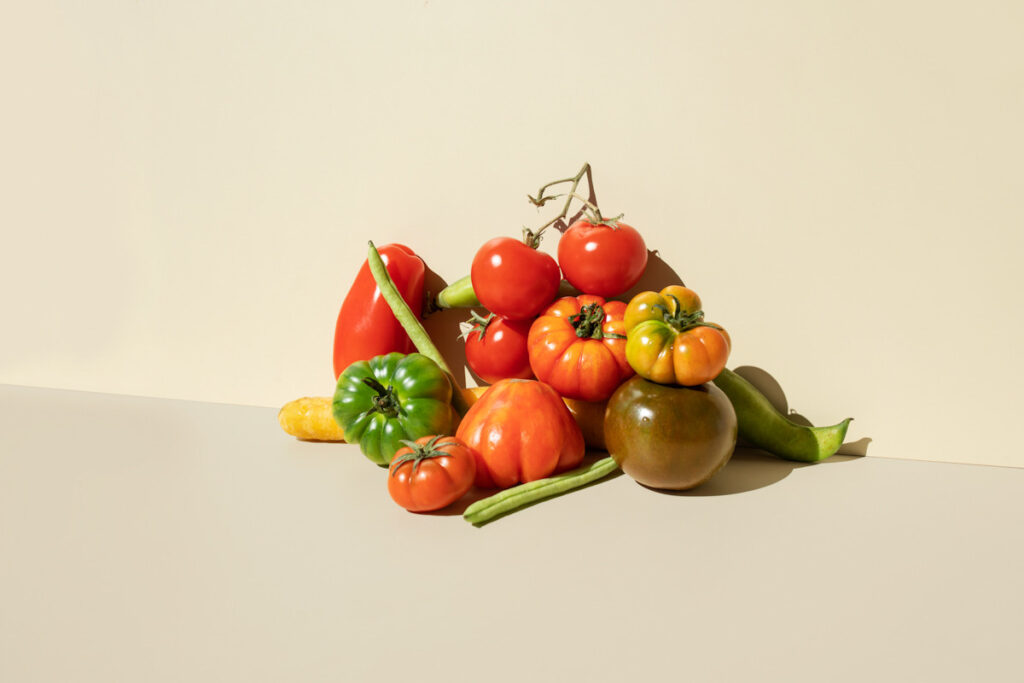 Photo shows a pile of fresh produce, including green beans and vibrant, varied tomatoes. Here are some of the science-backed benefits of a plant-based diet.