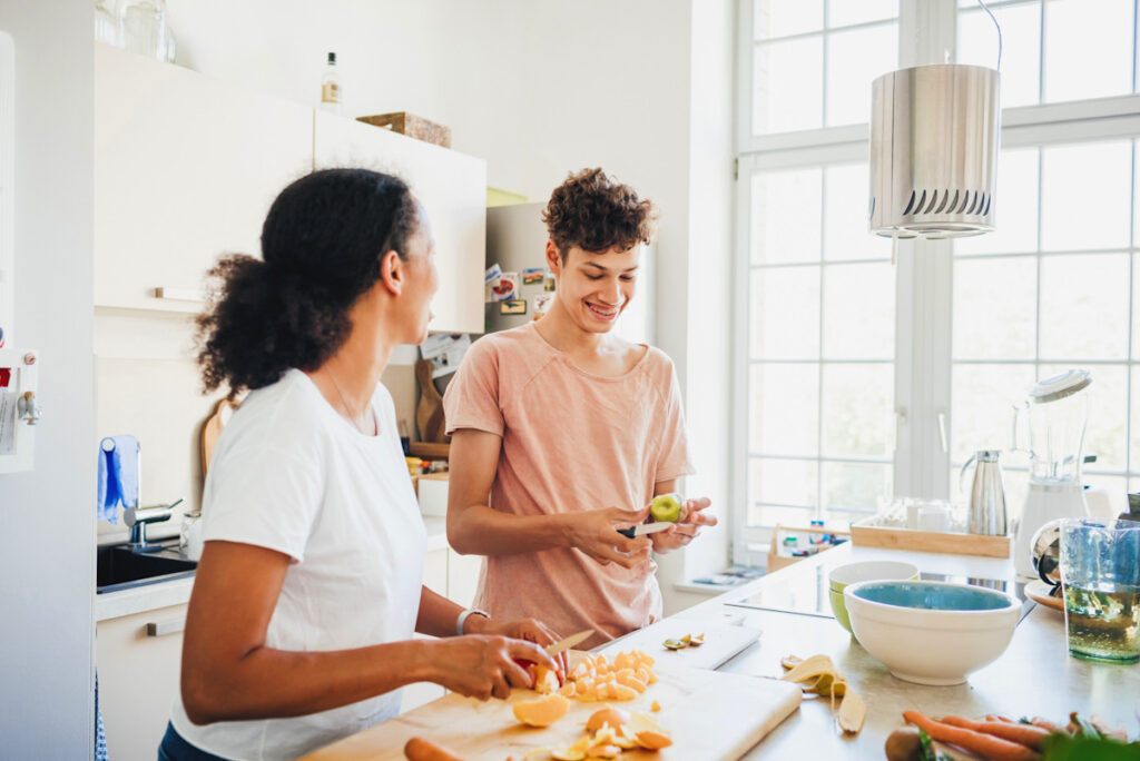 Photo shows two people preparing food at home.