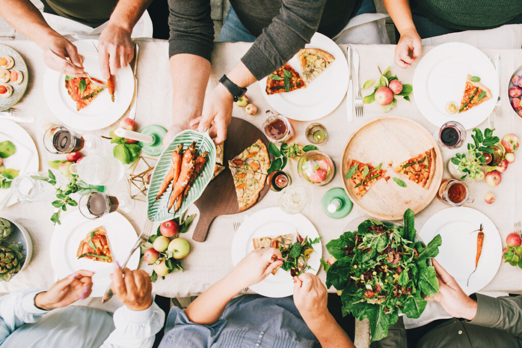Photo is an overhead shot of a table with many people sat sharing food and passing plates.