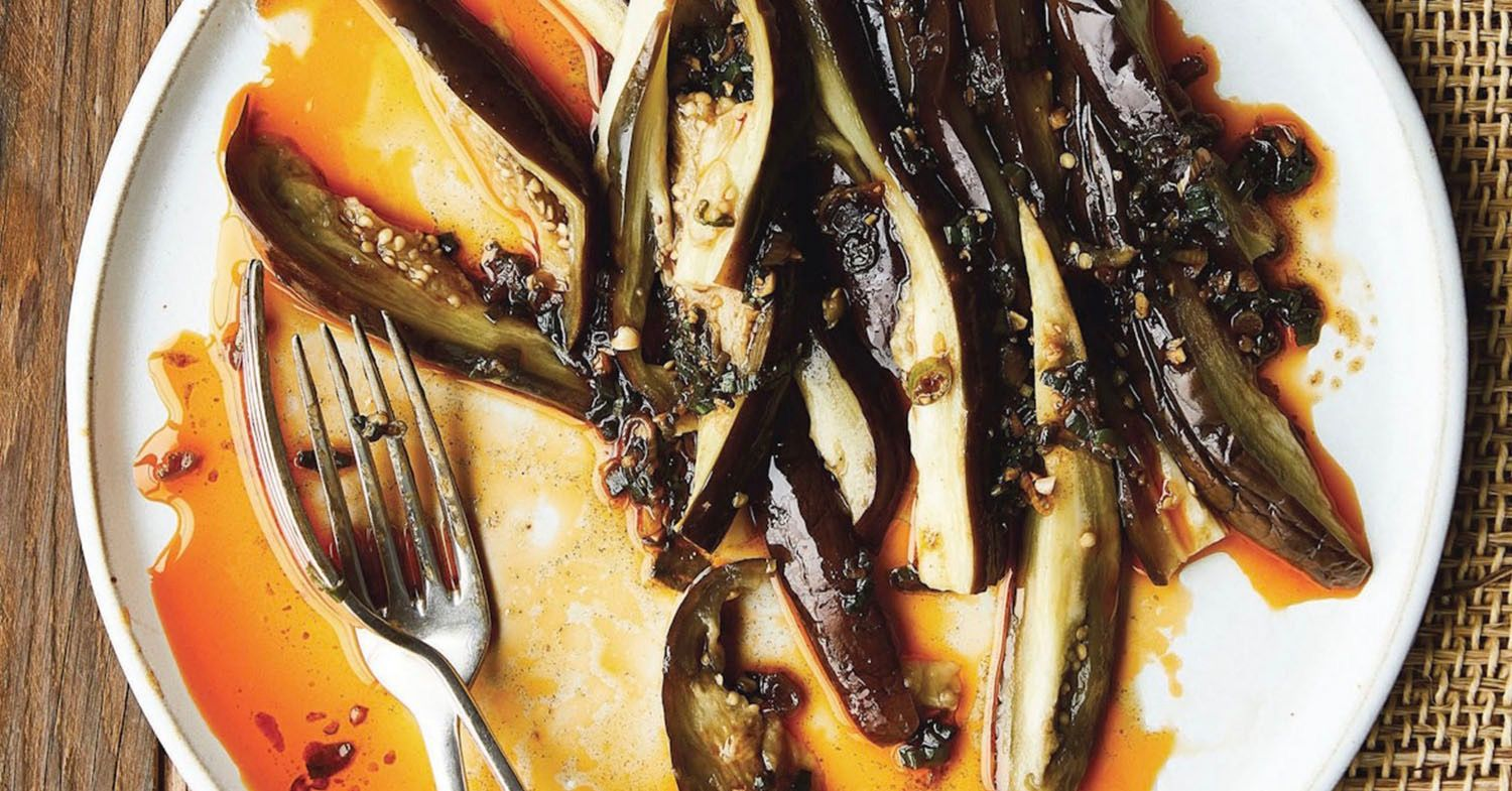 The eggplant on a plate served with a smoky green onion oil sauce.