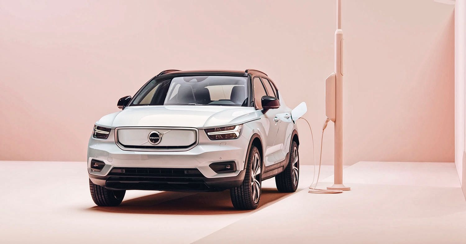 Photo of a silver Volvo electric car charging against a pink background