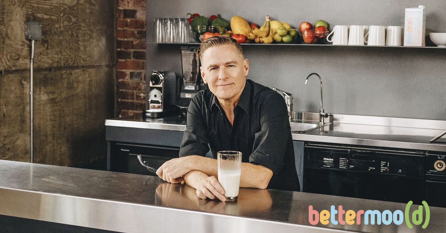 Photo shows Bryan Adams drinking a glass of Bettermood's Moo Drink—a plant-based oat milk.