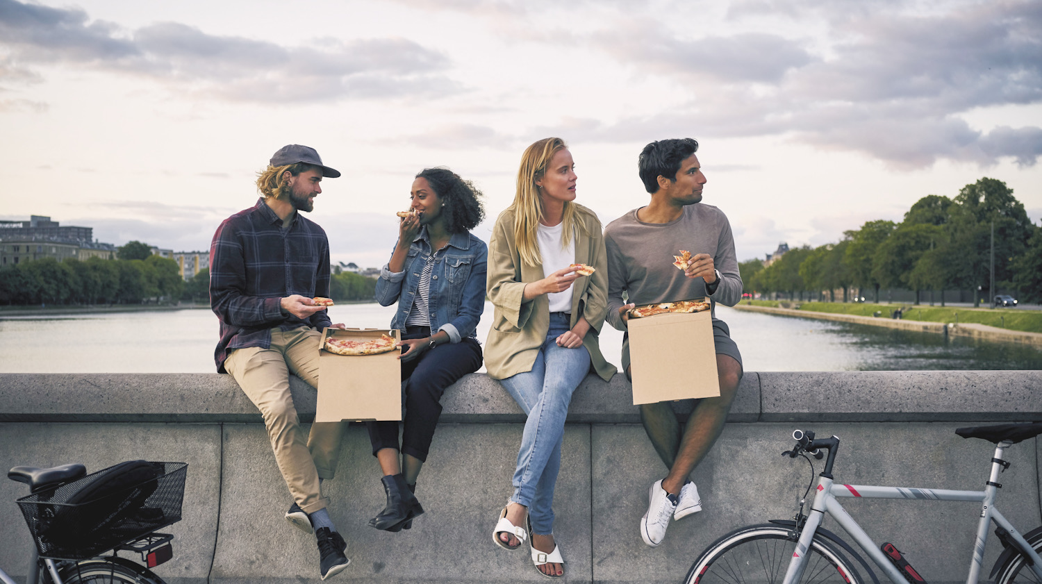Photo shows a group of young people eating together outside next to a lake. Denmark's new climate plan aims to tackle the impact of climate change through food.