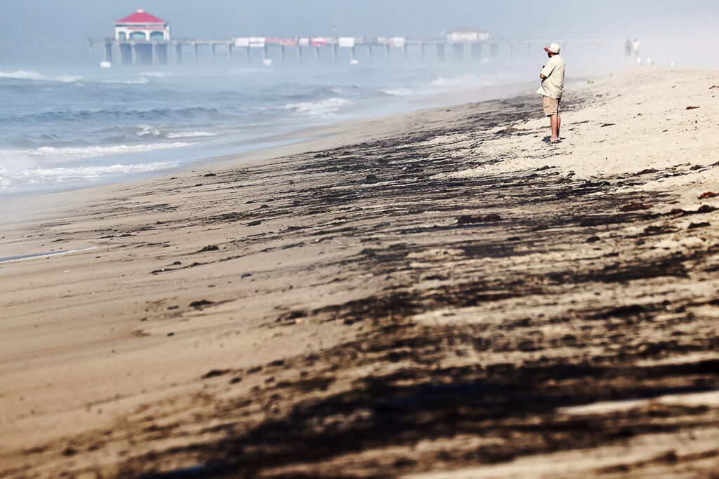 Photo shows someone standing on a beach with what appears to be tar-like stains on the sand.