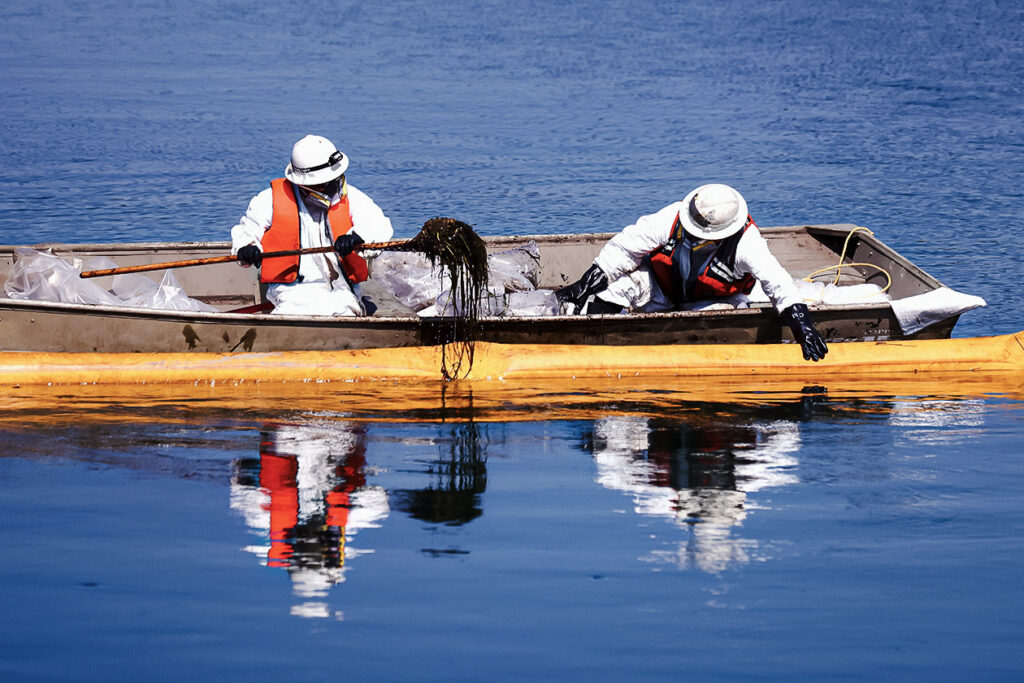 Photo shows two people in protective gear cleaning the oily water.