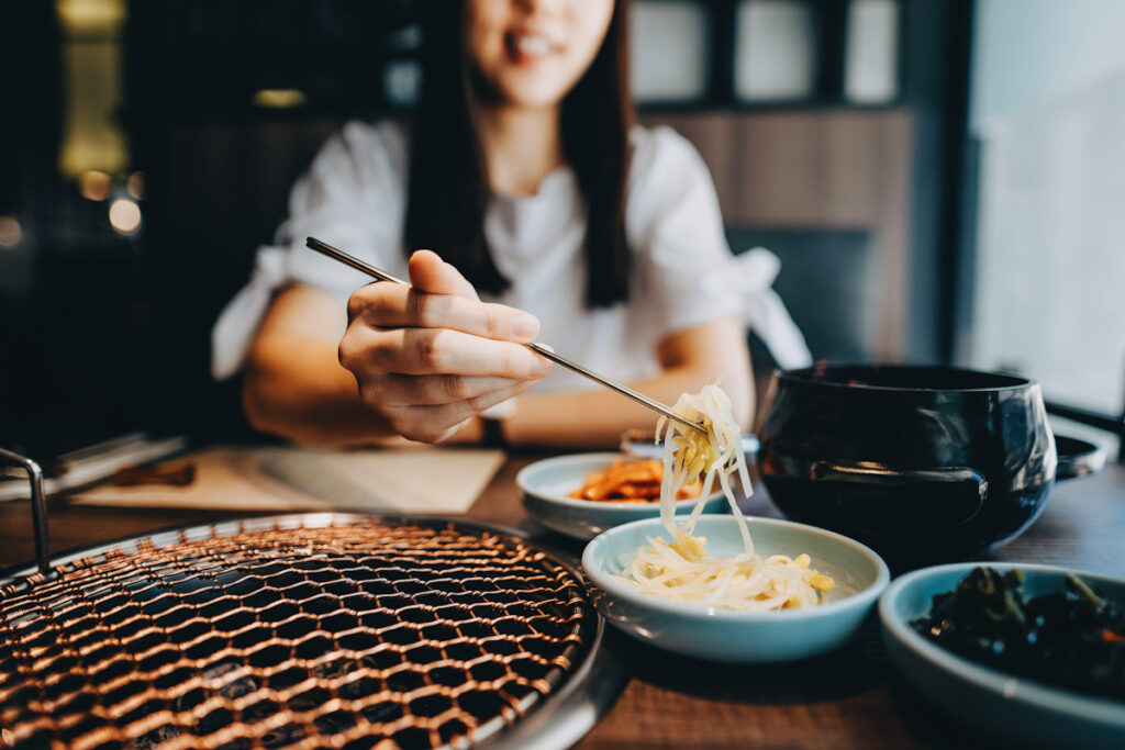 Photo shows a young Asian woman eating a beansprout-based Korean appetitizer.