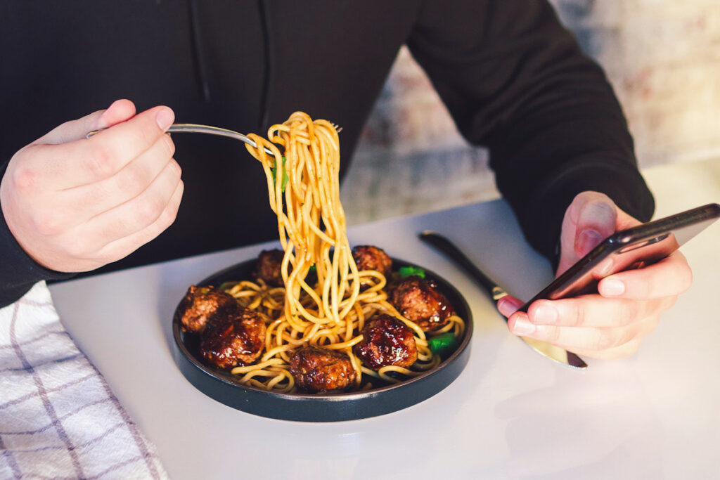 Photo shows someone looking at their phone and eating meatballs with spaghetti at the dinner table. Eating more vegan food (or adopting a flexitarian diet) comes with several benefits.