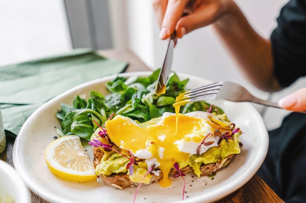 Photo shows real egg on toast along with a fresh salad, lemon, and avocado.