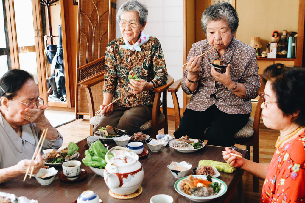 Photo shows a group of Okinawan women eating a traditional lunch together around a low table. One of the most commented-upon benefits of a flexitarian diet is increased longevity.