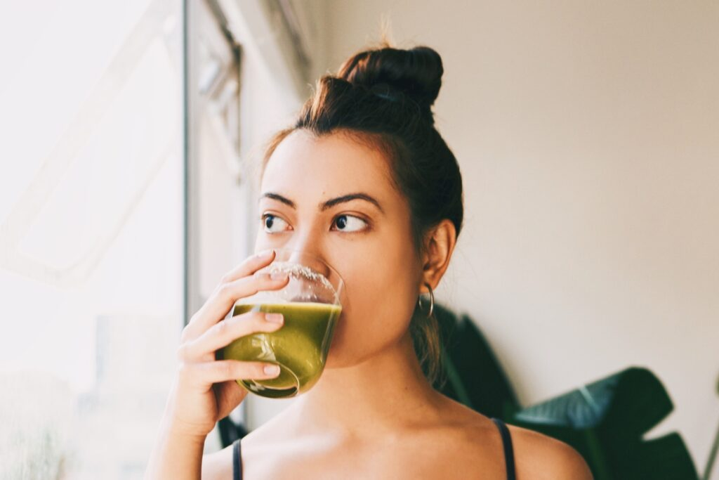Photo shows a woman drinking a green smoothie.