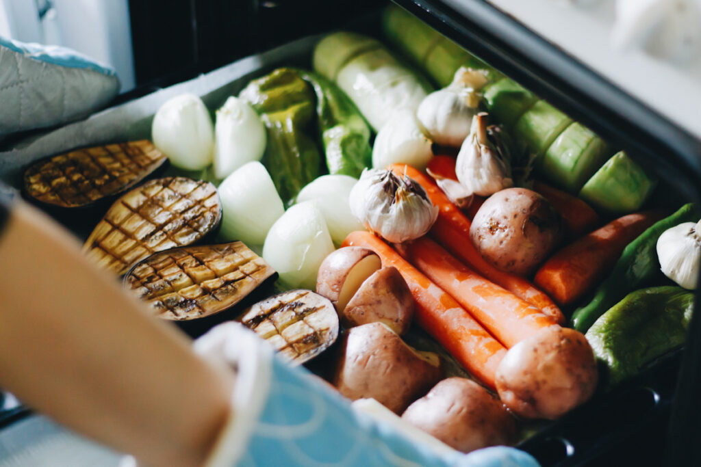 Photo shows someone taking a tray of fresh baked vegetables out of an oven. Here's how to use your sheet pan to make anything.