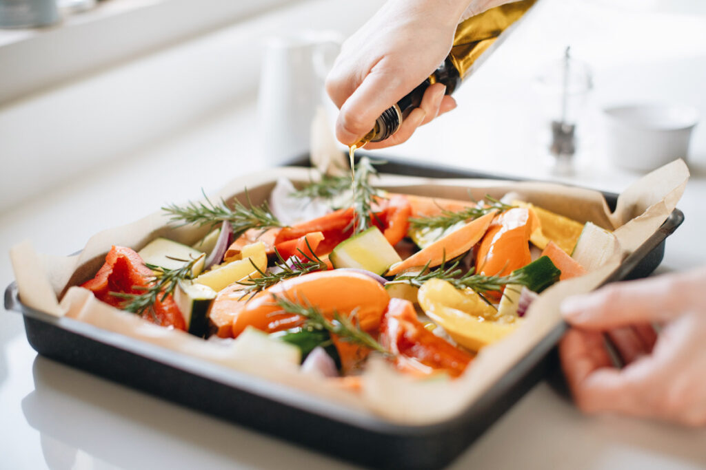 Photo shows someone pouring olive oil over a sheet pan full of vegetables and seasoning, ready to go in the oven.