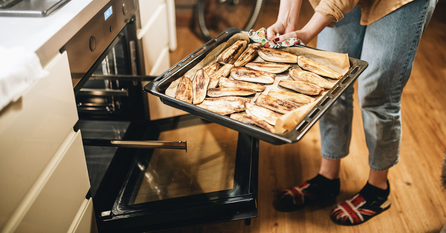 Photo shows someone taking a sheet pan of baked and glazed aubergine out of the oven.