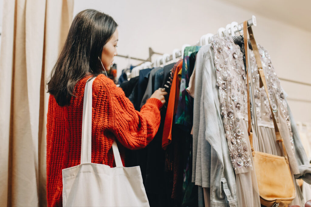 Photo shows someone shopping at a rail of clothing. Are you still an ethical vegan if you go thrifting for leather?