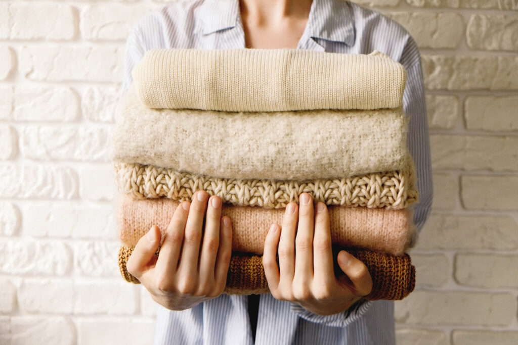 Photo shows a person holding a stack of folded clothes to her chest, including wool-like sweaters.