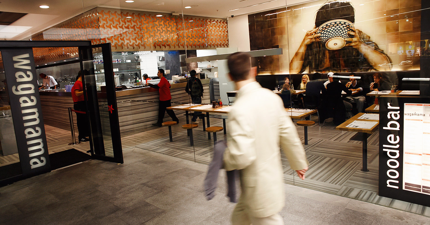 Photo shows a customer walking past the clear glass front of a Wagamama restaurant.